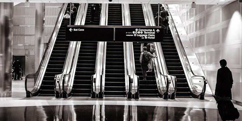 People rising on escalator